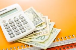 calculator and dollar bills on spiral notebooks