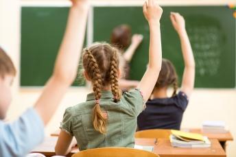 kids in classroom hands raised